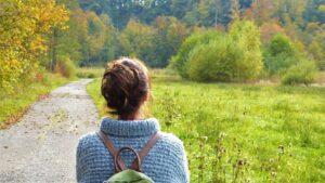 Frau mit Rucksack spaziert durch herbstliche Landschaft