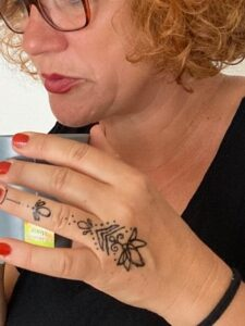 Frau mjit Tattoo auf Hand und Ringfinger