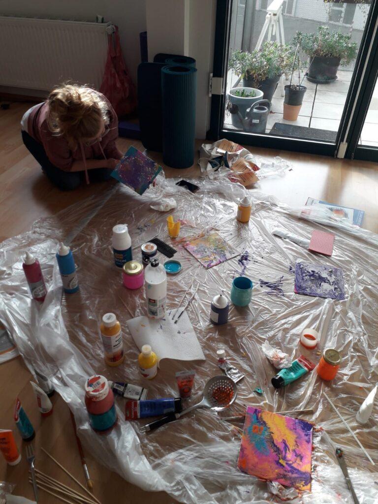 Dagmar hockt auf dem Boden zwischen vielen Farbdosen